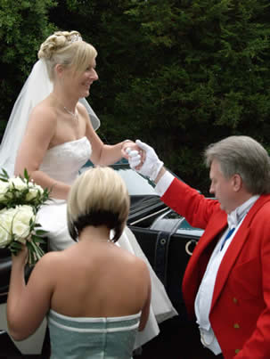 Wedding toastmaster helping bride from carriage as she arrives for her wedding reception