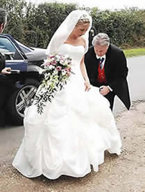 English toastmaster Richard Palmer assisting a bride with her wedding dress as she arrives at the church